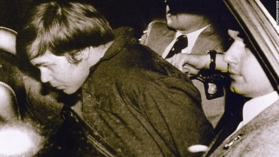 "Hinckley is escorted by police following his arrest.  He was obsessed with actress Jodie Foster, haven written to her from his hotel room earlier that day, ""There is a definite possibility that I may be killed in my attempt to get Reagan."" Hinckley wrote he was doing this to try to win her love."