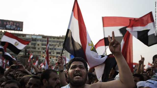 Muslim Brotherhood members and supporters of deposed president Mohamed Morsi shout slogans waving national flags during a rally outside Rabaa al-Adawiya mosque on July 15, 2013 in Cairo, Egypt. A top US official pressed Egypt's interim leaders for a return to elected government after the army ousted Morsi, whose supporters massed to rally for his return. AFP PHOTO/GIANLUIGI GUERCIA (Photo credit should read GIANLUIGI GUERCIA/AFP/Getty Images)