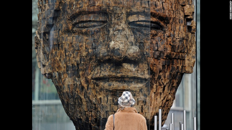 <strong>GERMANY:</strong> A woman views a giant wooden head of Mandela in the city center of Essen in western Germany. Created by artist Jems Robert Koko Bi from the Ivory Coast, the sculpture is made of burned spruce wood and is supposed to stand for the fight for freedom.