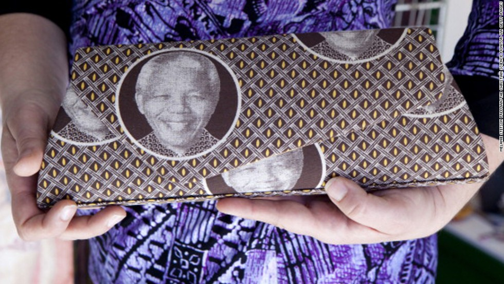<strong>SOUTH AFRICA:</strong>  A woman holds a purse with Mandela's face on it in Johannesburg.