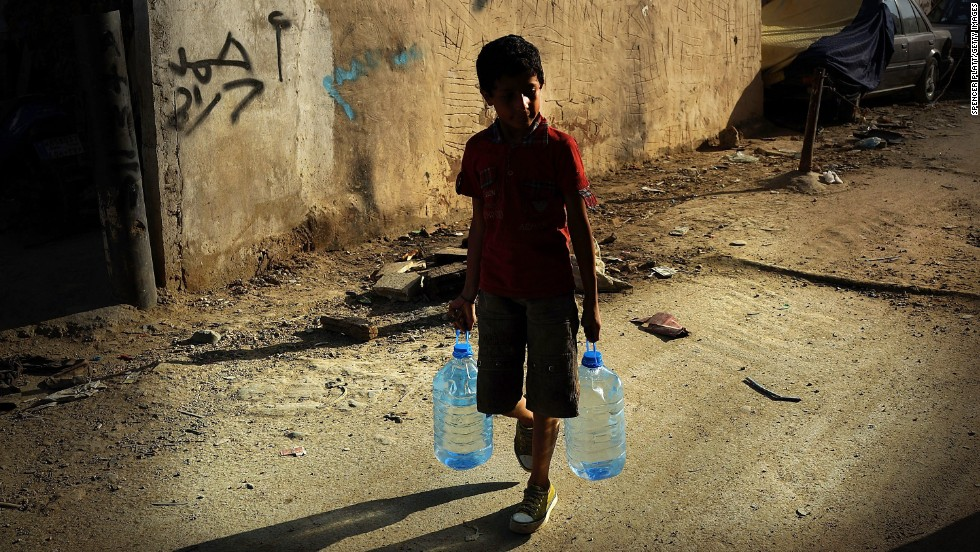 A boy walks with jugs of water in a Beirut neighborhood with a high concentration of Syrian refugees.