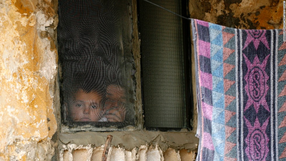A Syrian woman and child look out of a refugee camp window in Alman, Lebanon, in June 2013.