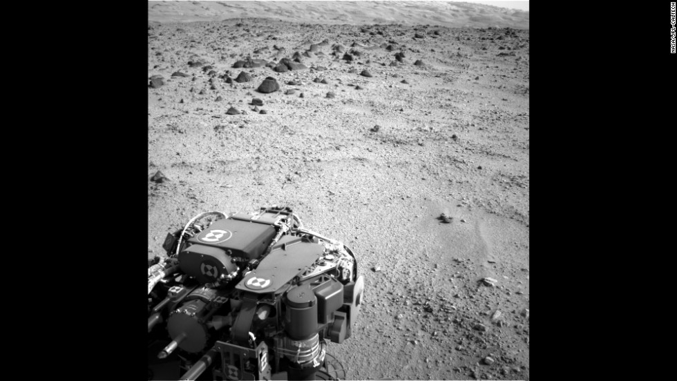 The lower slopes of Mount Sharp are visible at the top of this image, taken on July 9, 2013. The turret of tools at the end of the rover's arm, including the rock-sampling drill in the lower left corner, can also be seen.