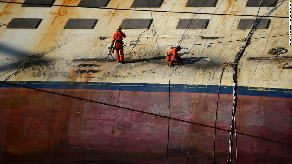 Workers stand on the edge of the ship on January 8, 2013.