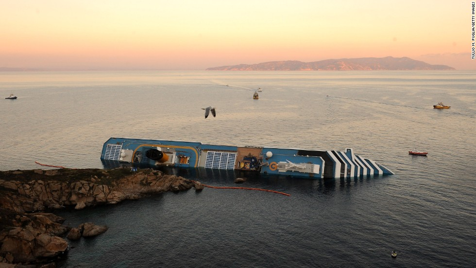 A bird flies overhead the Costa Concordia on January 18, 2012. Rescue operations were suspended as the ship slowly sank farther into the sea.