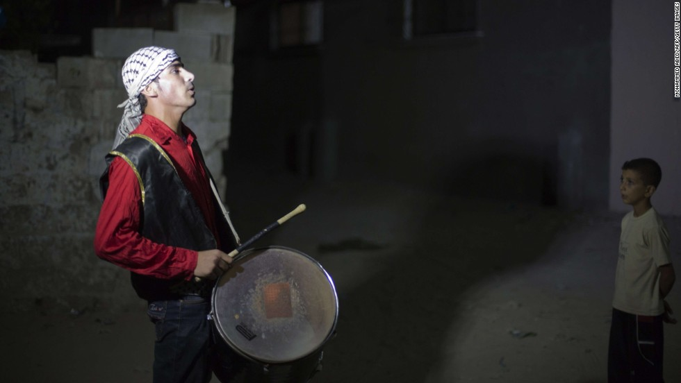 Public waker Mohammad al-Jamalah rouses people with his drum in Gaza City, signaling the time for the pre-dawn meal before fasting begins again on July 18.