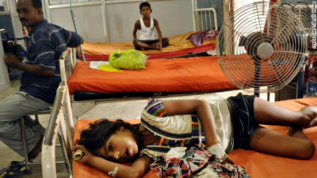 An Indian child (foreground), who consumed a free mid day meal at a school in the Saran district of Bihar state, reacts while resting at a ward as a parent (L) and another schoolchild (background) look on at the Patna Medical College and Hospital in Patna on July 18, 2013. Thousands of school children were refusing free meals in poverty-stricken eastern India, fearful of being poisoned, after 22 children died from eating lunch apparently contaminated with insecticide, officials said July 18. AFP PHOTO (Photo credit should read STRDEL/AFP/Getty Images)