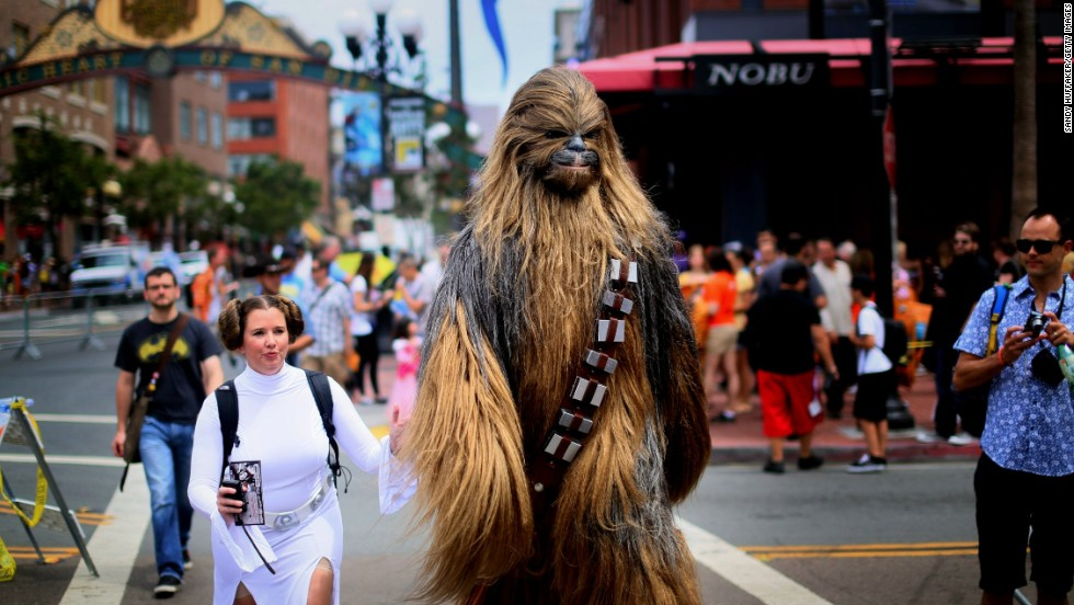 "Fans dressed as ""Star Wars"" characters Princess Leia and Chewbacca walk down San Diego's 5th Avenue."