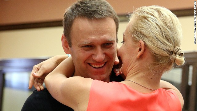 Russia's top opposition leader Alexei Navalny hugs his wife Yulia in the courtroom in Kirov on July 19, 2013.