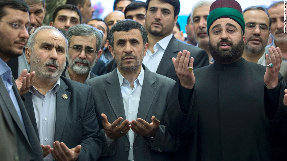 Outgoing Iranian President Mahmoud Ahmadinejad, center, prays at the holy shrine of Imam Abbas in Karbala, Iraq, on Friday, July 19, during the second Friday of Ramadan.