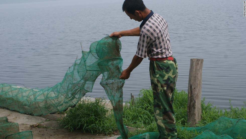 """Kong Guoqing cleans a fishing net near a sinkhole """"lake."""" Kong's family have been farmers on the rich soil of northern China plain for five generations. He is the first one in the family to start a fishing business."""