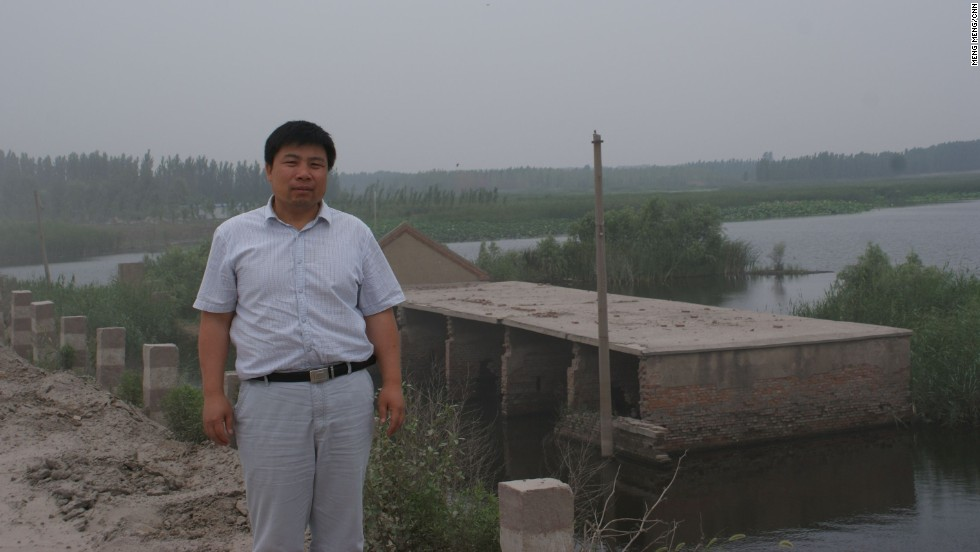 Xiao Guoqiang, a 50-year-old farmer stands before his sunken village in Jining, Shandong Province on June 26, 2013. Underground mining in this region is devouring 20 million square meters of land a year.