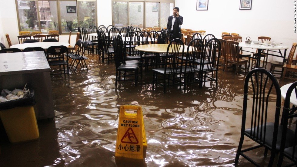 A man tries to make a phone call on Friday, July 19, in a flooded restaurant in Kunming, China, in the wake of Typhoon Soulik.