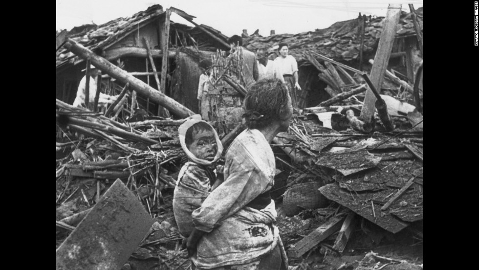 A woman and child wander among debris in Pyongyang, North Korea, after an air raid by U.S. planes, circa 1950. The war began on June 25, 1950, when the North Korean People's Army crossed the 38th parallel and easily overwhelmed South Korean forces in a surprise attack.