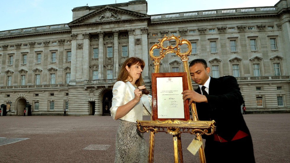The queen's press secretary, Ailsa Anderson, left, and Badar Azim, a palace footman, place the official birth announcement on a golden easel in front of Buckingham Palace on July 22.
