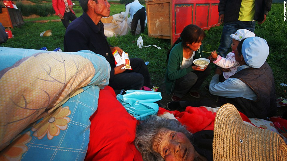 """JULY 23 - MAJIAGOU, CHINA: Survivors of a deadly earthquake in northwest China's Gansu province eat instant noodles in a clearing after their homes were damaged. At least <a href=""""http://cnn.com/2013/07/21/world/asia/china-quake/index.html?hpt=ias_c2"""">89 people died and 600 others were injured</a> in the quake, according to state media."""