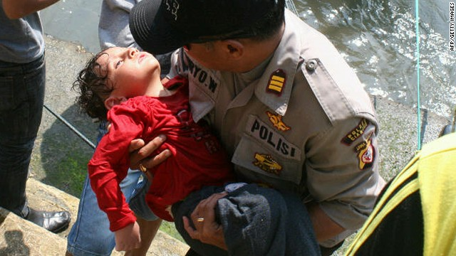 An Indonesian police man carries an exhausted young boy from the water near Cidaun, West Java on Wednesday.