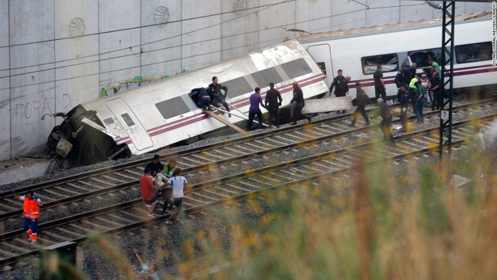 Rescuers work to clear a derailed car.
