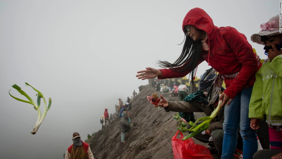 A worshipper throws an offering of vegetables into the caldera. Hundreds of people travel to the volcano to pray on the 14th day of the festival.