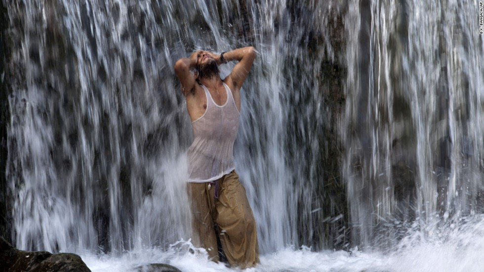 A man fasting for Ramadan cools off in a waterfall on July 25 in Islamabad, Pakistan.