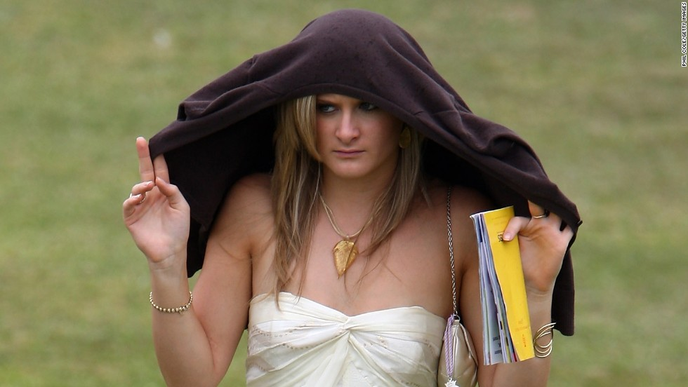 A female racegoer shelters from the rain at Glorious Goodwood where the English summer can often bring inclement weather.