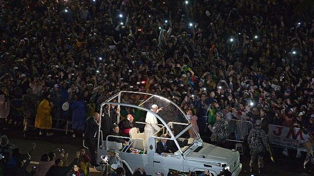 Pope Francis arrives on the popemobile at Rio de Janeiro's iconic Copacabana beachfront on July 25, 2013 for his welcome to World Youth Day ceremonies. On the fourth day of his visit to Brazil and borne along by adoring crowds, Pope Francis waded into the country's ramshackle slums and onto the front line of its fierce national battle over poverty and corruption, before going to the much wealthier district of Copacabana for his welcome by the youth. AFP PHOTO / GABRIEL BOUYSGABRIEL BOUYS/AFP/Getty Images