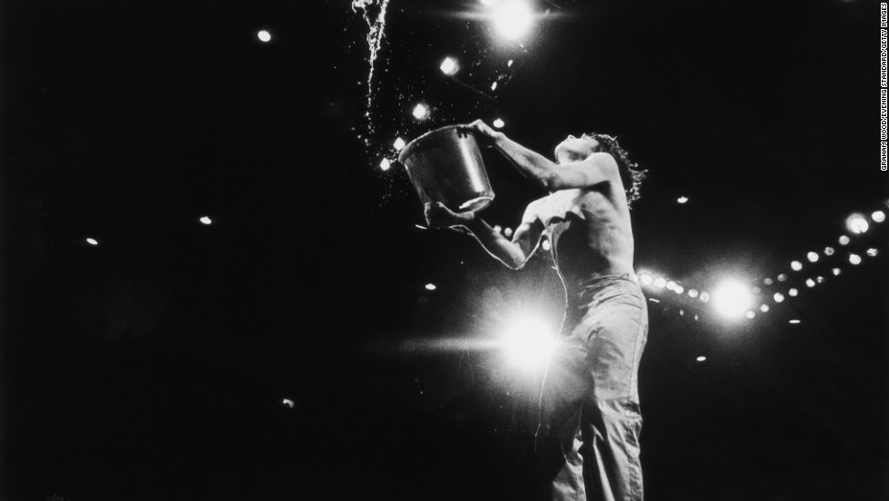 Mick Jagger empties a bucket of water on stage at the 1976 Knebworth Festival in Hertfordshire, England.
