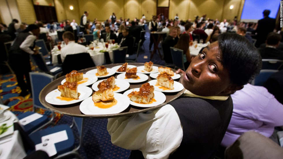 A waitress serves dessert to a table of the 300-plus attendees.