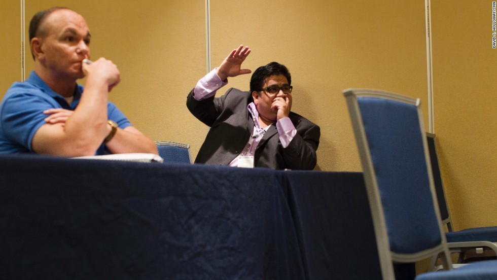 Texas delegate Artemio Muniz raises his hand during a session. Although he disagrees with some GOP members on immigration reform, he says he became a Republican because of his conservative beliefs.