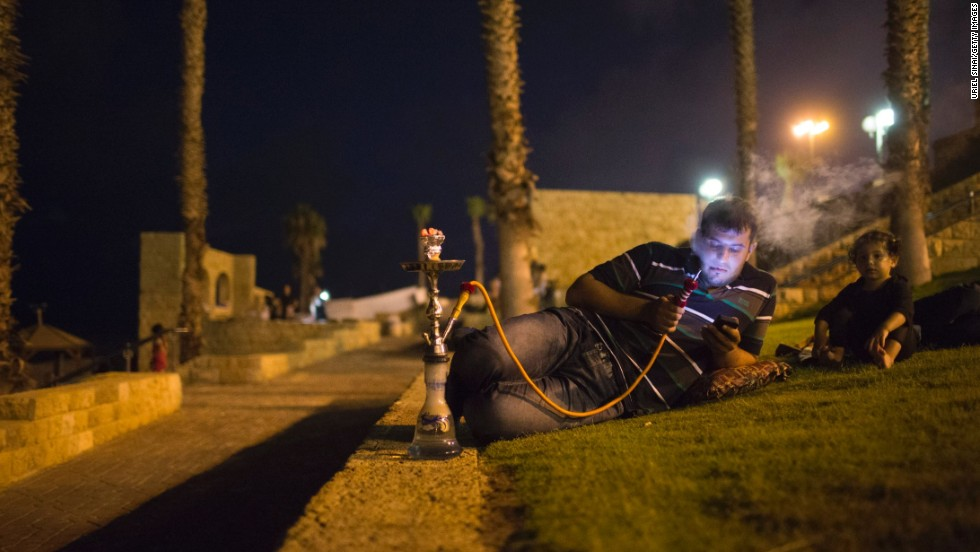 A man smokes a hookah Thursday, July 25, in Jaffa, a suburb of Tel Aviv, Israel, as Muslim worshipers break their daylong fast.