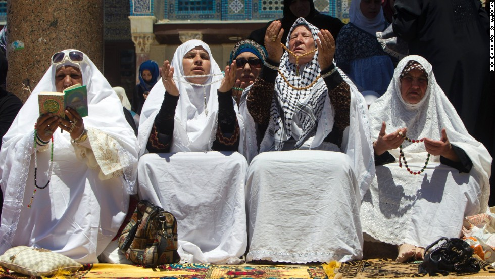 Palestinian women hold prayer beads as they pray outside the Dome of the Rock at al-Aqsa Mosque compound in Jerusalem on Friday, July 26.