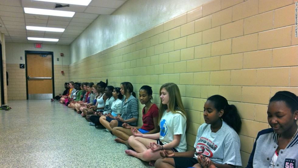 Students at Druid Hills Middle School in Dekalb Country, Georgia, inhale and exhale deeply to control their breathing as they sit in lotus pose.
