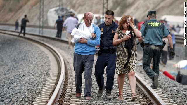 "In this photo taken on Wednesday July 24 2013, Wounded people are evacuated at the site of a train accident in Santiago de Compostela, Spain. Spanish police on Friday detained the driver of a train that crashed in northwestern Spain, lowered the death toll from 80 to 78 and took possession of the ""black box"" of the train expected to shed light on why it was going faster than the speed limit on the curve where it derailed. And in an interview with The Associated Press, an American passenger injured on the train said he saw on a TV monitor screen inside his car that the train was traveling 194 kph (121 mph) seconds before the crash — far above the 80 kph (50 mph) speed limit on the curve where it derailed. (AP Photo/La Voz de Galicia/Monica Ferreiros)"
