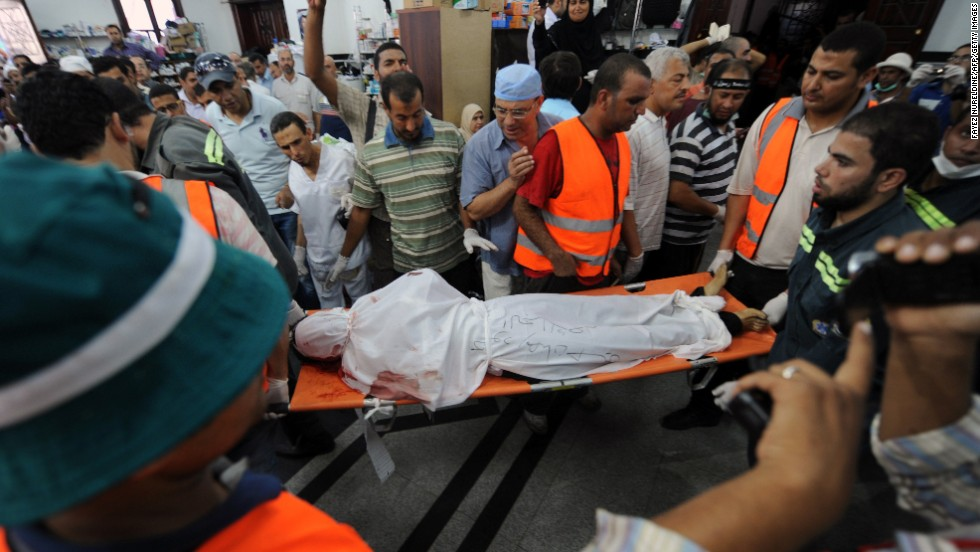 The body of a Muslim Brotherhood protester, reportedly shot dead after violence erupted the night before, is moved as mourners watch inside a field hospital in Cairo on July 27.