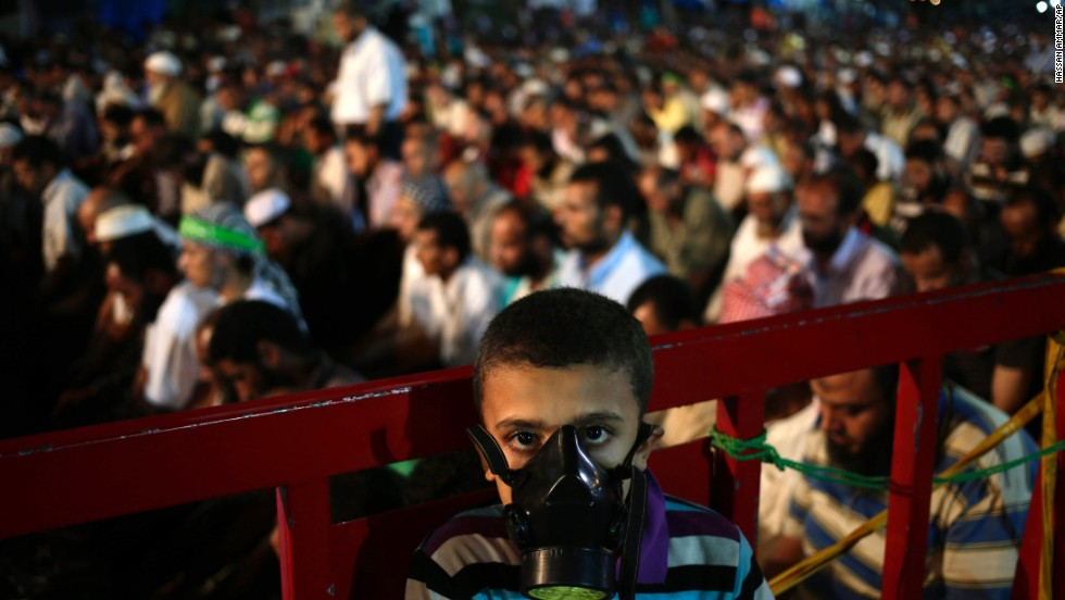A boy wears a tear gas mask as supporters of Egypt's ousted President Mohammed Morsy pray at the camp set up by supporters in the Nasr City area of Cairo on July 28.