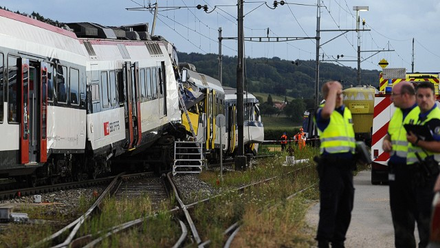 Rescuers stand on the site of a train accident on July 29, 2013 in Granges-pres-Marnand, western Switzerland. Two trains collided head-on, injuring 40 passengers, at least five of them seriously, police said. AFP PHOTO / ALAIN GROSCLAUDEALAIN GROSCLAUDE/AFP/Getty Images