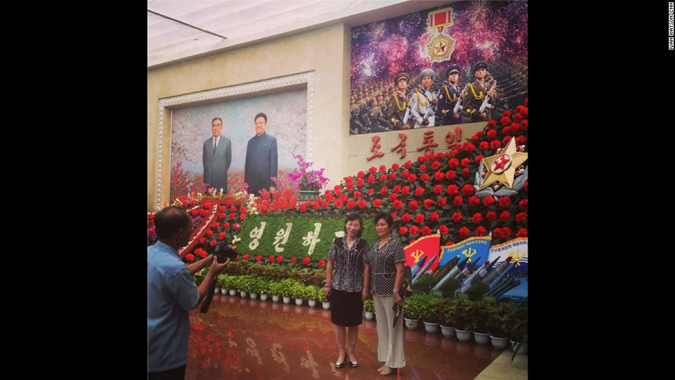 """This was most tightly controlled restricted foreign assignment of my career,"" Watson said of his visit to the country. Here <a href=""http://instagram.com/p/cNgHU6CDbv/"" target=""_blank"">visitors take souvenir photos</a> at the Kimilsungia and Kimjongilia flower festival. The flowers are named after former North Korean leaders Kim Il Sung and Kim Jong Il, who overlook the scene from the painting on the left hand side."