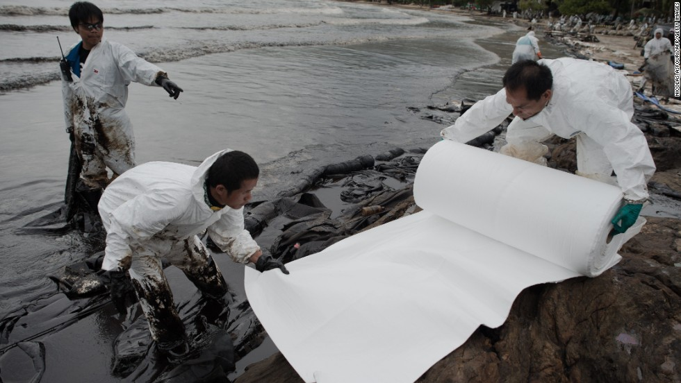 Thai navy personnel work to clean up the oil spill on Ao Phrao beach on July 30.