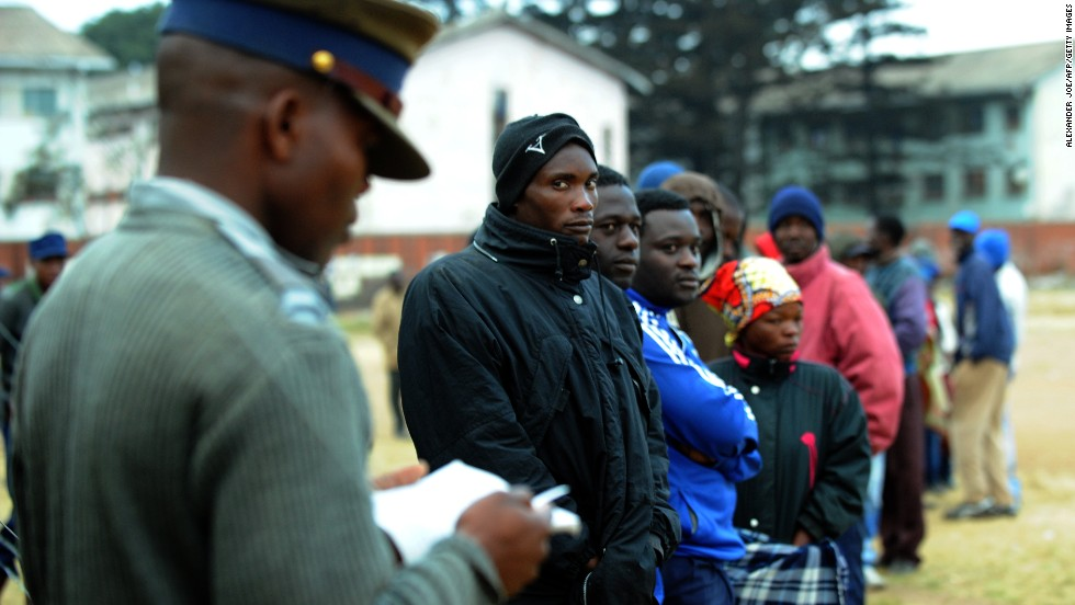 A policeman stands as Zimbabweans line up near a polling station in Harare. Zimbabwe was readying for an inadequately prepared yet tight election battle that could see President Robert Mugabe extend his 33-year grip on power.