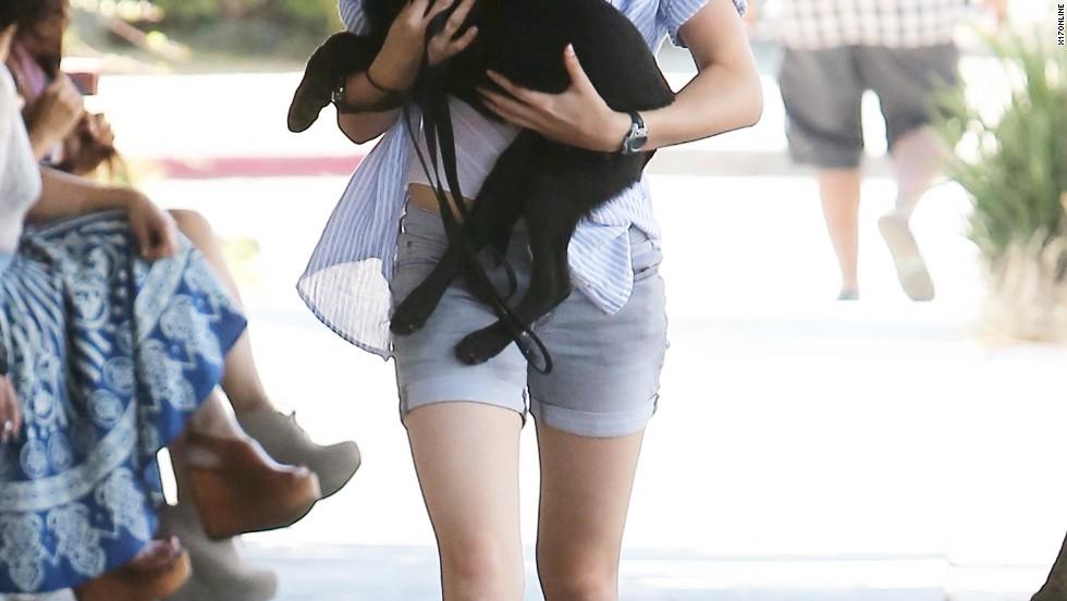 Kristen Stewart cuddles with a cute pup while walking through Long Beach on July 29.