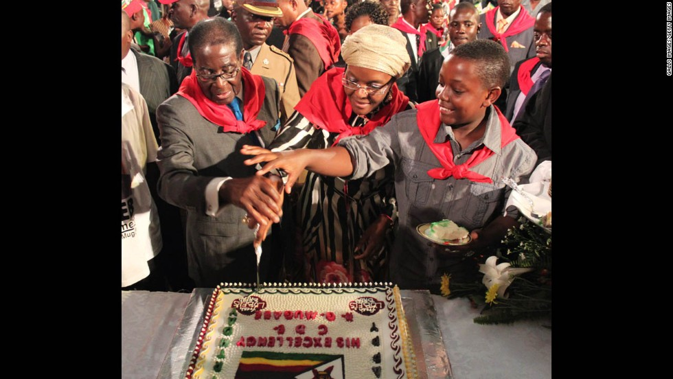 Mugabe cuts his birthday cake, with wife Grace and son Bellarmine Chatunga, during celebrations for his 87th birthday in February 2011 in Harare.