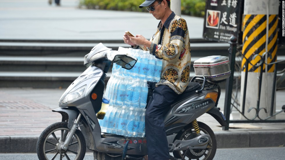 A man ferries several cases of bottled water on his scooter as a heat wave continues in Shanghai on July 24.