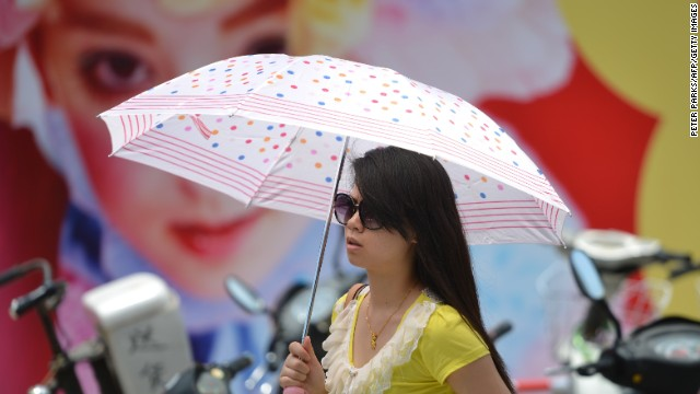 A woman holds an umbrella to protect herself from the sun as a heatwave hits Shanghai on July 4, 2013. The Shanghai Meteorological Bureau issued heatwave warnings as temperatures reached as high as 38 degrees celcius in the city in recent days according to state run media. AFP PHOTO/Peter PARKS (Photo credit should read PETER PARKS/AFP/Getty Images)