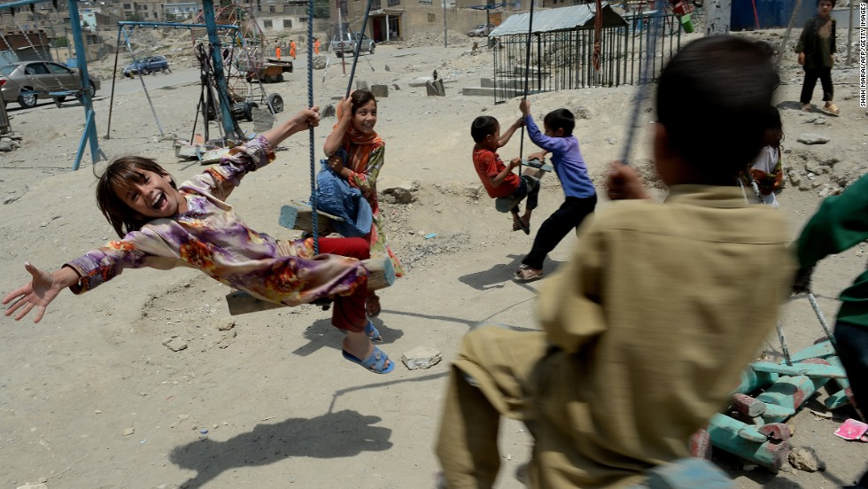 "August 1 - KABUL, AFGHANISTAN: Children play on a swing near a cemetery in Kabul. The number of civilians killed in Afghanistan increased by nearly a quarter in the first six months of this year, the <a href=""http://cnn.com/2013/07/31/world/asia/afghanistan-civilian-casualties/index.html?hpt=ias_c2"">United Nations said in a report</a>. Most of the 1,319 civilians killed so far this year were victims of the Taliban."