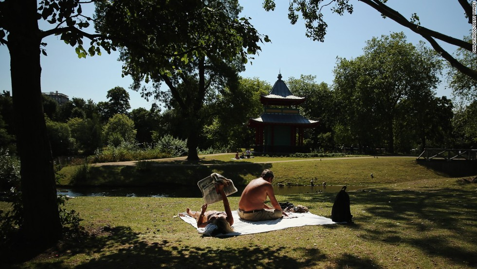 People relax in the sun in Victoria Park in London, on Thursday, August 1.