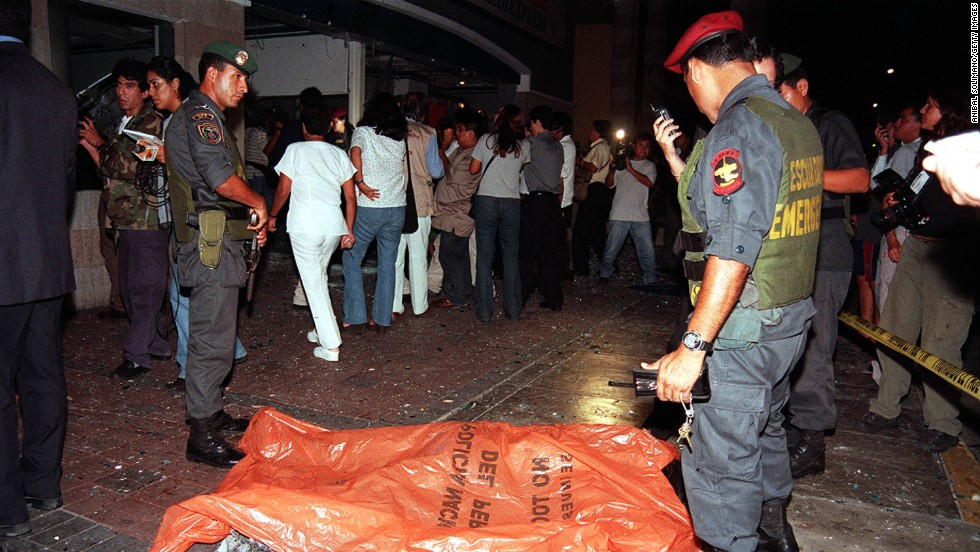 "Police officers stand next to the body of a victim after a car bomb exploded on March 20, 2002, at a shopping center near the <a href=""http://archives.cnn.com/2002/WORLD/americas/03/21/peru.embassy.blast/"">U.S. Embassy in Lima, Peru,</a> killing nine people."
