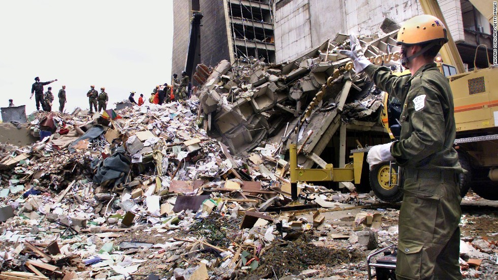 "Rescue workers stand on the remains of a building in front of the <a href=""http://www.cnn.com/WORLD/africa/9808/08/africa.explosions.01/"">U.S. Embassy in Nairobi, Kenya,</a> on August 10, 1998, four days after a deadly attack. Twelve Americans were among more than 200 people killed in nearly simultaneous bombings at U.S. embassies in Nairobi and Dar es Salaam, Tanzania."