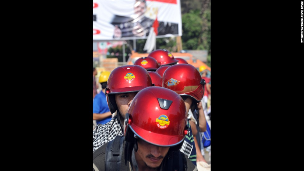 Morsy supporters in red helmets march during a protest against the government in Cairo on August 2. Pro-Morsy marches began after Friday prayers, when supporters made their way back to their camp outside the Rabaa al-Adawiya mosque.