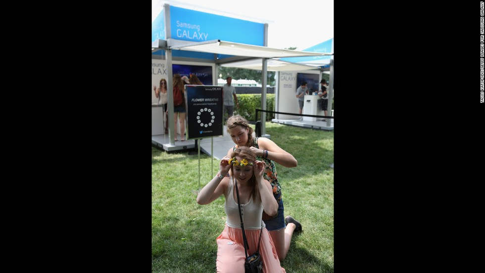 An attendee helps another adjust her headband at the festival on August 3.