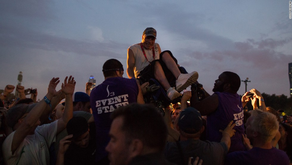 A crowd surfer in a wheelchair is helped over a barricade while the band Nine Inch Nails performs on Friday, August 2.